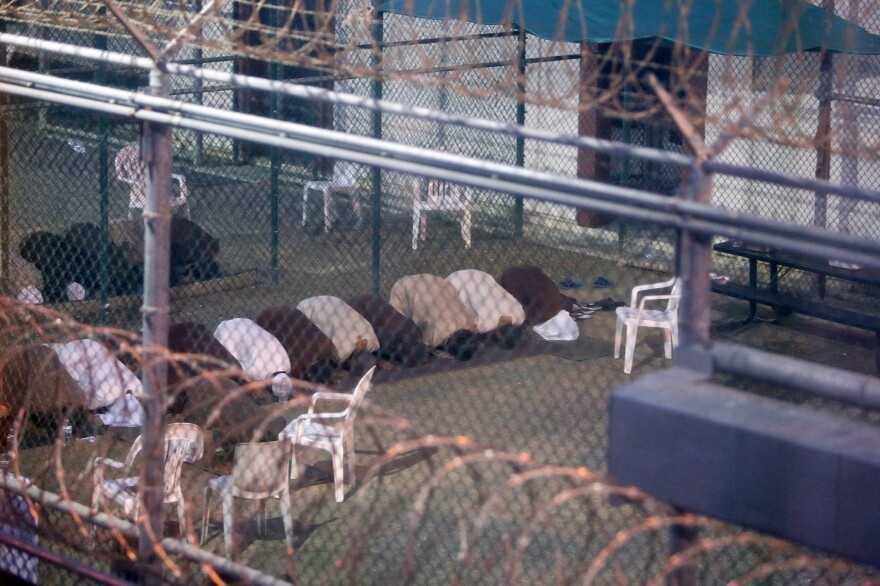 Captives separated by a fence conduct communal evening prayers at the Camp 6 prison building at the U.S. Naval Base at Guantanamo Bay, Cuba.