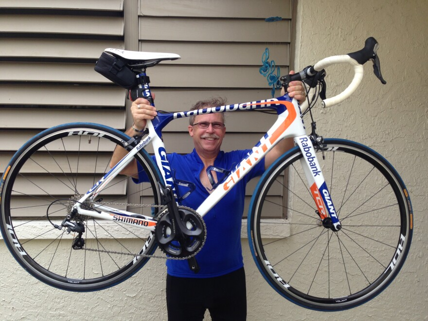 A smiling man holding a bike aloft