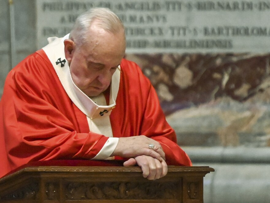 Pope Francis prays as he celebrates Palm Sunday Mass behind closed doors in St. Peter's Basilica. Italy's lockdown to mitigate the spread of the novel coronavirus prohibits public gatherings, including religious services.