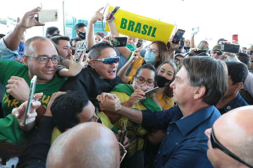 Brazilian President Jair Bolsonaro stops to take pictures with supporters during the inauguration ceremony of the BR-469 highway development on Aug. 27 in Foz do Iguaçu, Brazil.