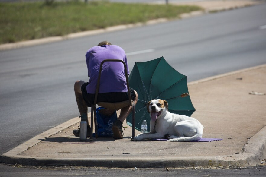 A man with his dog sitting at the intersection of Airport and I-35.
