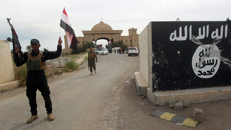 Iraqi Shiite fighters in Tikrit pose in front of a former presidential palace that had been held by the so-called Islamic State, which had painted its black banner at the entrance.