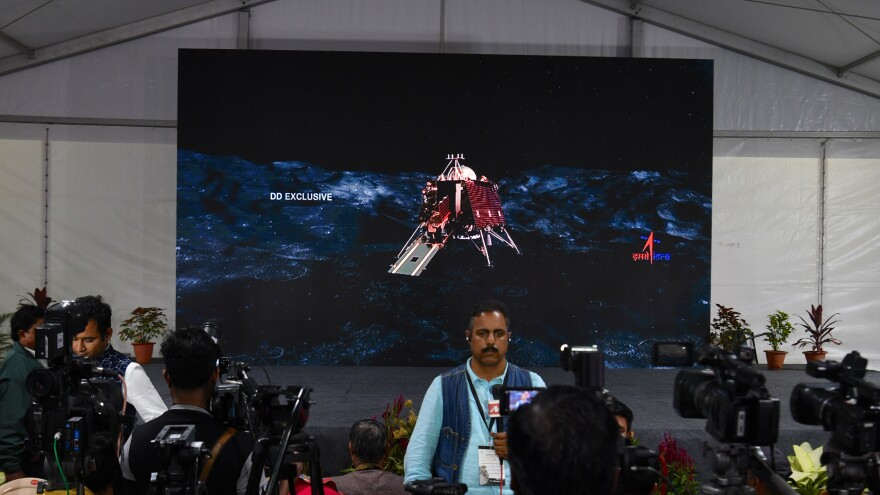 An illustration of the landing craft stands behind members of the media at an Indian Space Research Organisation facility this year in Bangalore, India. Authorities initially chalked up the failed landing in September to a loss of communication with the craft; last week, they revealed what happened to it.