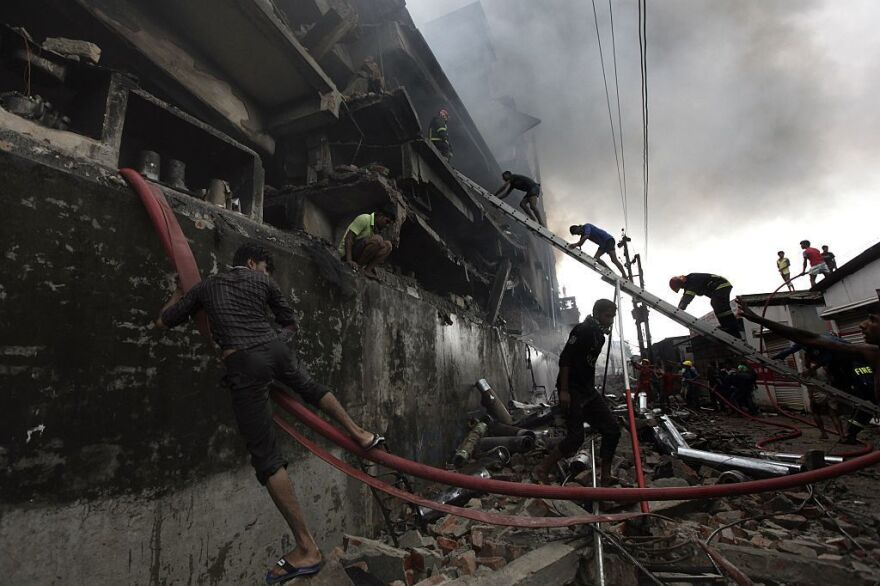 Bangladeshi firefighters and volunteers work to put out a fire and search for survivors at the site of an explosion in a factory in Tongi.