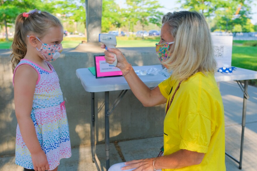 A teacher performs a temperature check on the first day of school. Some schools that have opened for in-person learning are struggling to find substitutes when teachers have to quarantine due to close contact with someone who has COVID-19.