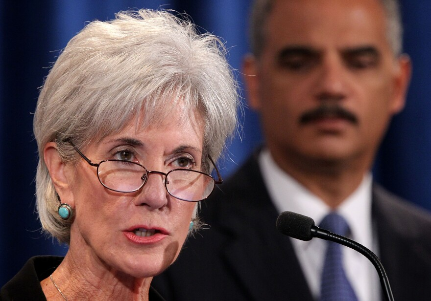 Health and Human Services Secretary Kathleen Sebelius speaks as Attorney General Eric Holder listens during a news conference last October. The two plan to remain in their current jobs as President Obama's second term begins.