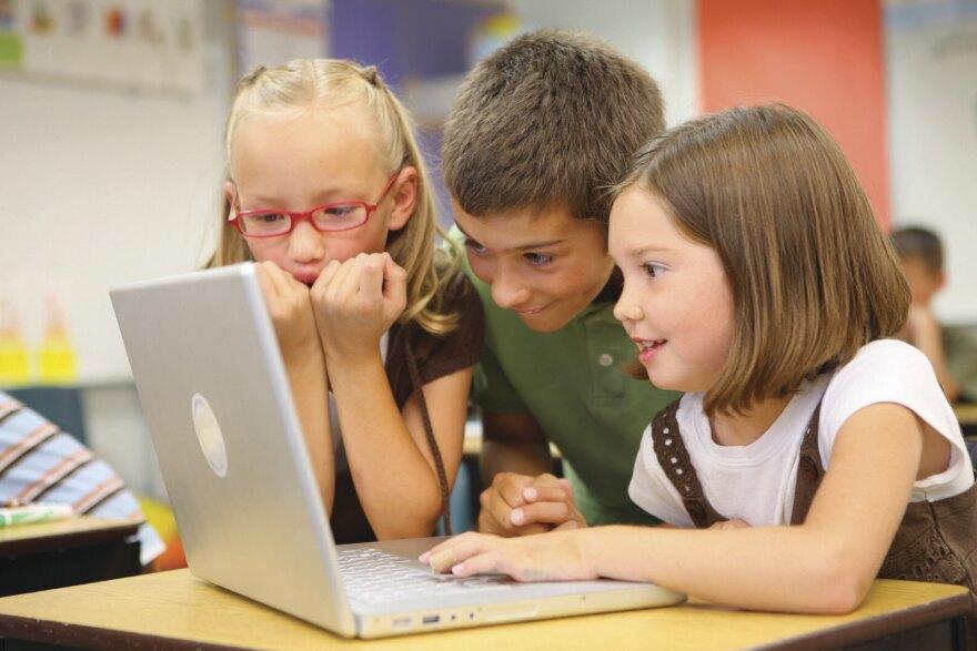 Three Children Work Togther On A Laptop