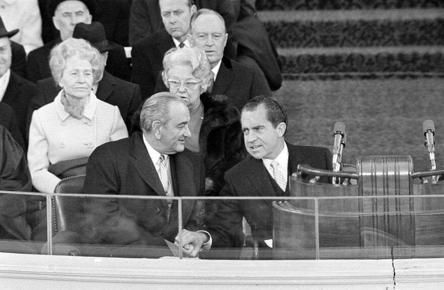 President Richard Nixon and former President Lyndon B. Johnson clasp hands as they sit on the inaugural stand where Nixon took the oath of office on Jan. 20, 1969.