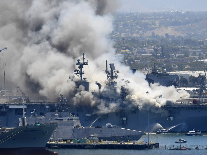 Smoke rises from the USS Bonhomme Richard at Naval Base San Diego in July, after an explosion and fire on board the ship. The Navy announced Monday the ship will be decommissioned.