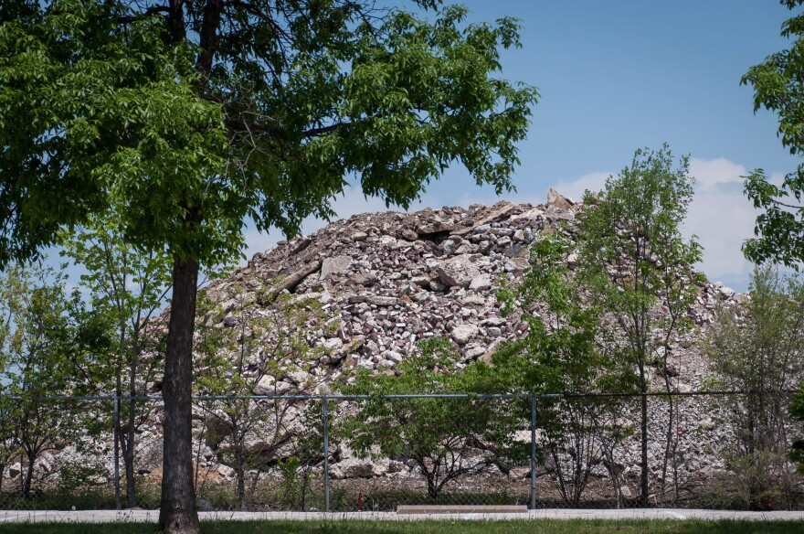 Parents and staff blame illnesses inside the Gateway school complex on debris brought over from the site of the planned National Geospatial-Intelligence Agency headquarters. The piles tower over a fence next to the school. May 6, 2018.