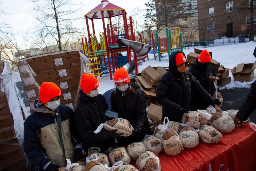 Volunteers hold turkeys during a giveaway for people in need, organized by Food Bank For New York City at Highbridge Houses in the Bronx on December 19, 2020 in New York. (Kena Betancur/AFP/Getty Images)