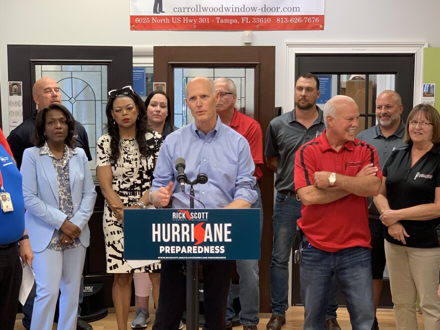 Senator Rick Scott stands at podium