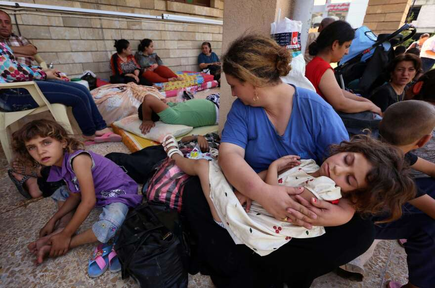 Iraqi Christians who fled violence in the village of Qaraqush rest upon their arrival at the St. Joseph church in the Kurdish city of Irbil.
