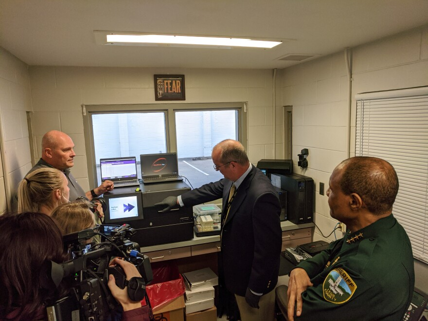 Officials from the Florida Department of Law Enforcement and Leon County Sheriff's Office demonstrate the automated DNA collection system.