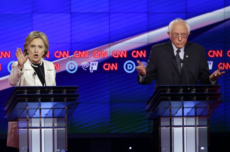 Democratic presidential candidates Sen. Bernie Sanders, I-V.t, right, and Hillary Clinton react as they speak during the CNN Democratic Presidential Primary Debate at the Brooklyn Navy Yard.