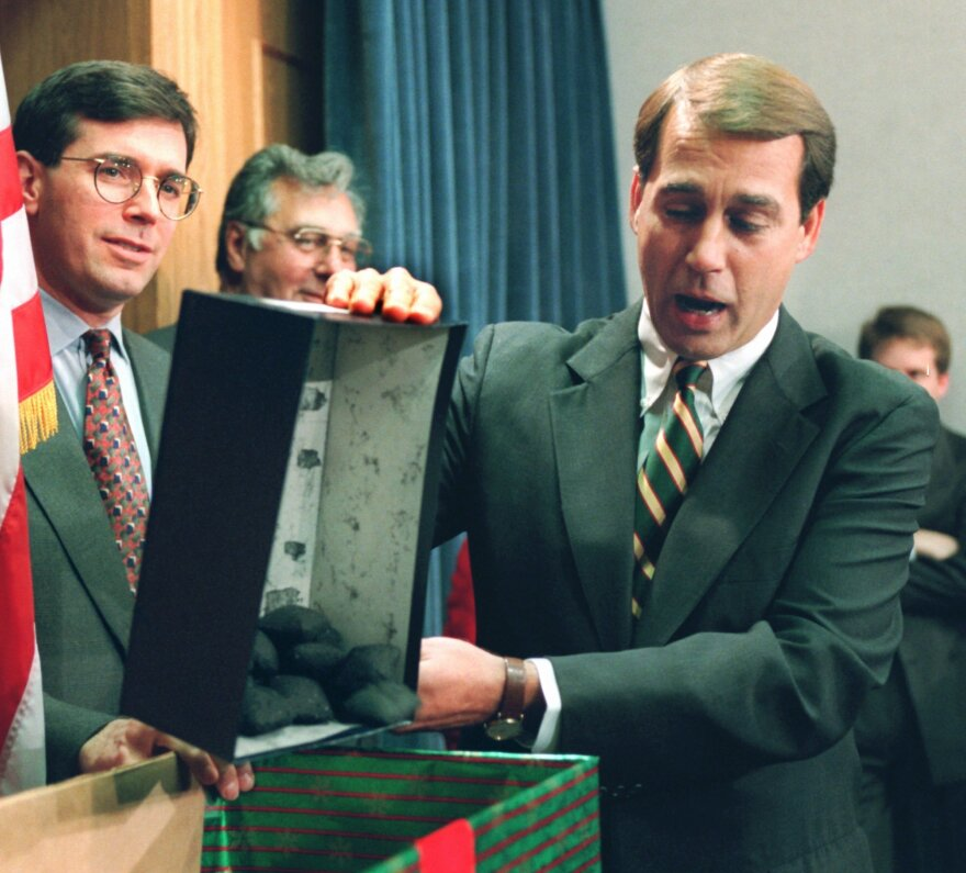 Then-Rep. John Boehner, R-Ohio, dumps out coal, which he called a Christmas gift to President Bill Clinton, during a Capitol Hill news conference on Dec. 21, 1995, during a government shutdown.
