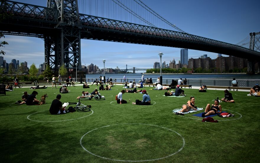 People relax in the sun while practicing social distancing last weekend in New York City's Domino Park. On Friday night, New York Gov. Andrew Cuomo issued an order loosening some of the state's coronavirus restrictions.