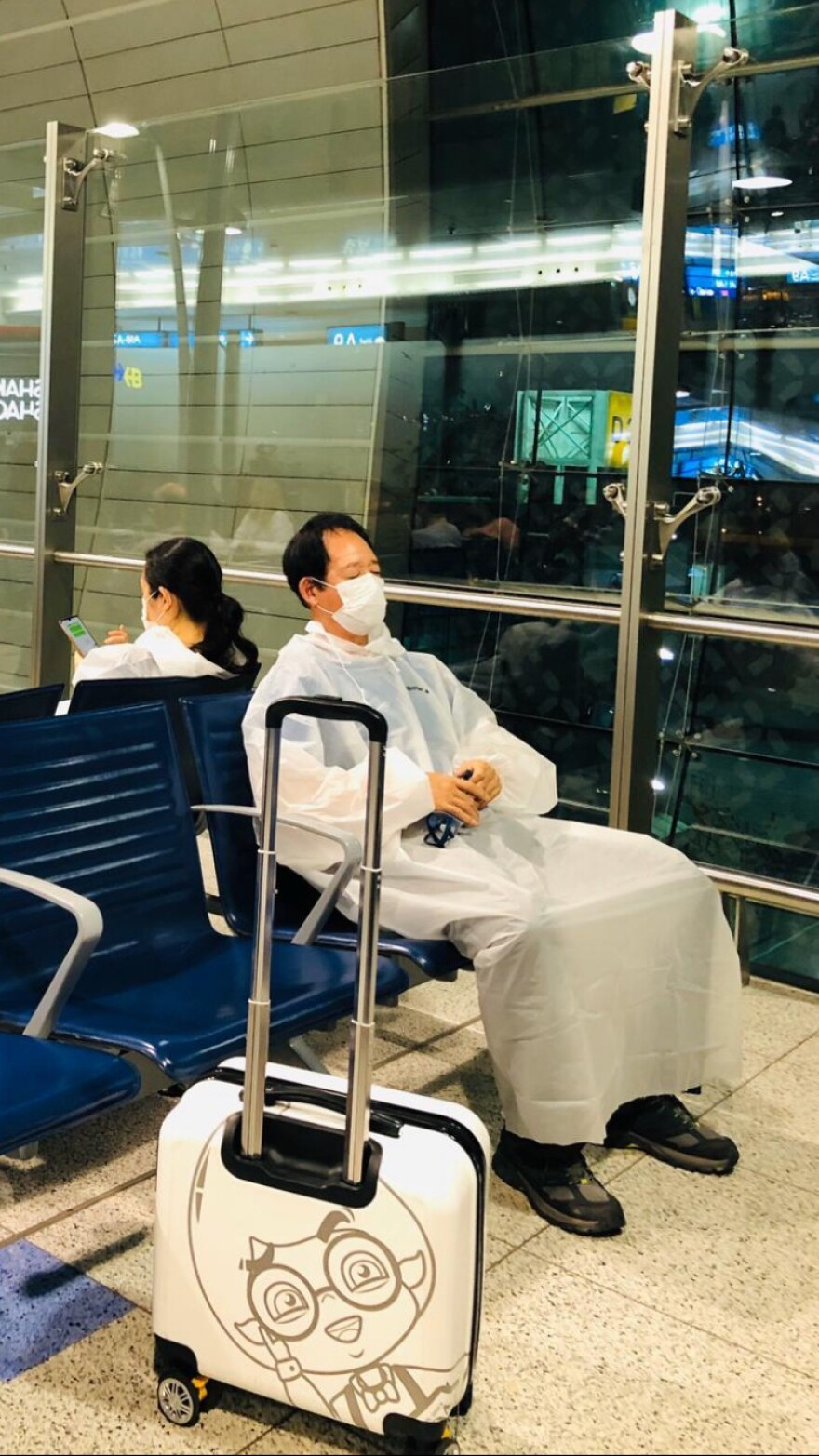 A man holding goggles in his hand as he sits and waits for a flight in the Dubai International Airport.  The man is also wearing a facial mask and a plastic suit that covers his entire body.