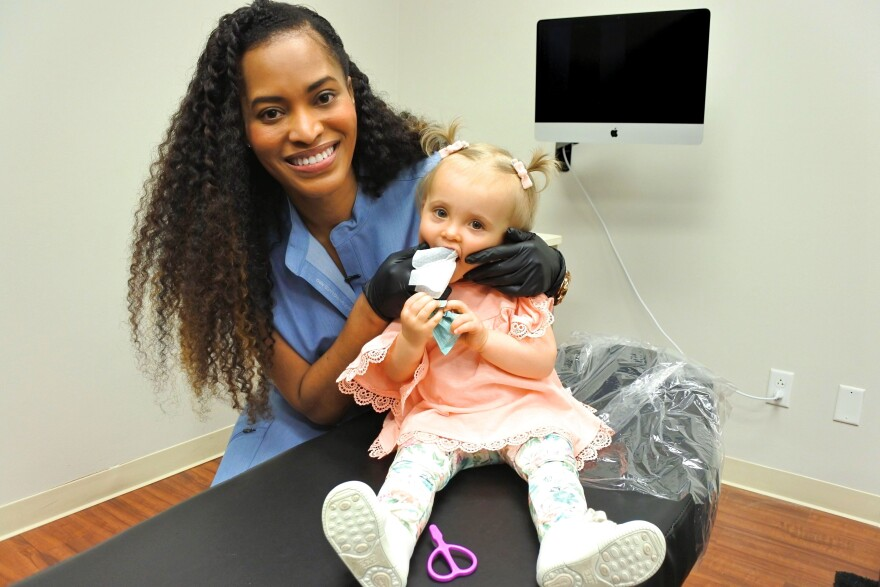 Dr. Misee Harris gives 1-year old Davi Spurlock her first dental exam.