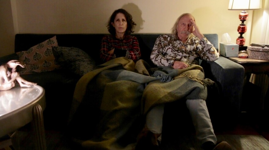 Photo of a woman and older man sitting on a sofa.