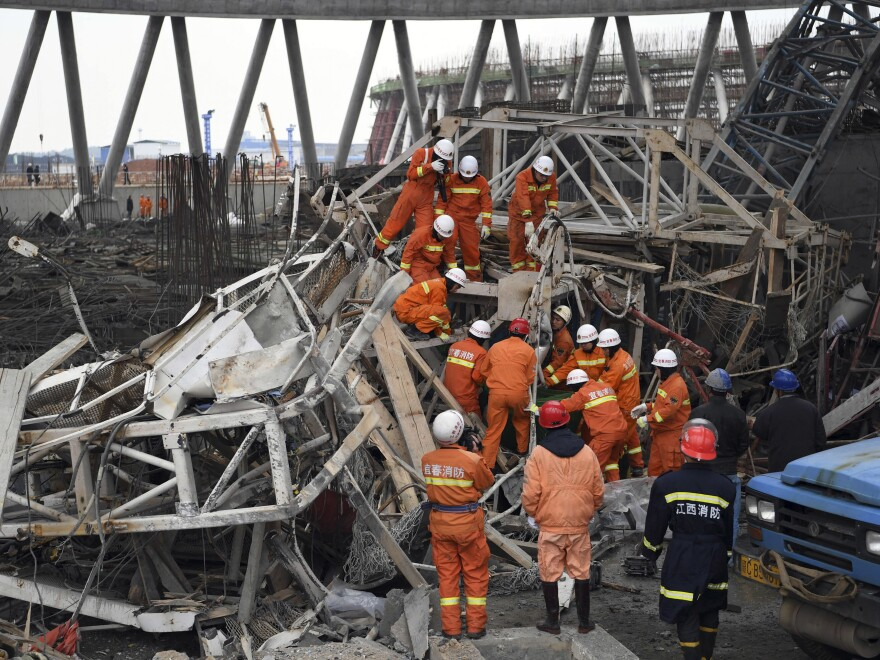 In this photo released by Xinhua News Agency, rescue workers look for survivors after a work platform collapsed at a power plant in eastern China's Jiangxi Province on Thursday.