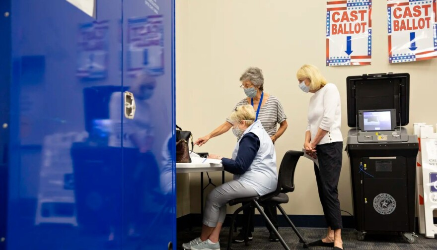 Poll workers help a voter in a voting booth