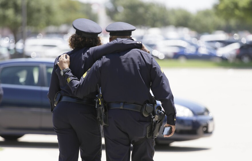 Dallas police officers comfort each other after the funeral for Dallas Police Senior. Cpl. Lorne Ahrens at Prestonwood Baptist Church in Plano, Texas, on Wednesday. Ahrens and four other officers were shot and killed during a protest two weeks ago in downtown Dallas.