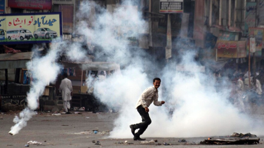 A demonstrator reacts after Pakistani policemen fire tear gas during a protest against power cuts in Karachi in June. Pakistan suffers from a massive energy crisis, one of several factors contributing to the country's severe economic troubles.