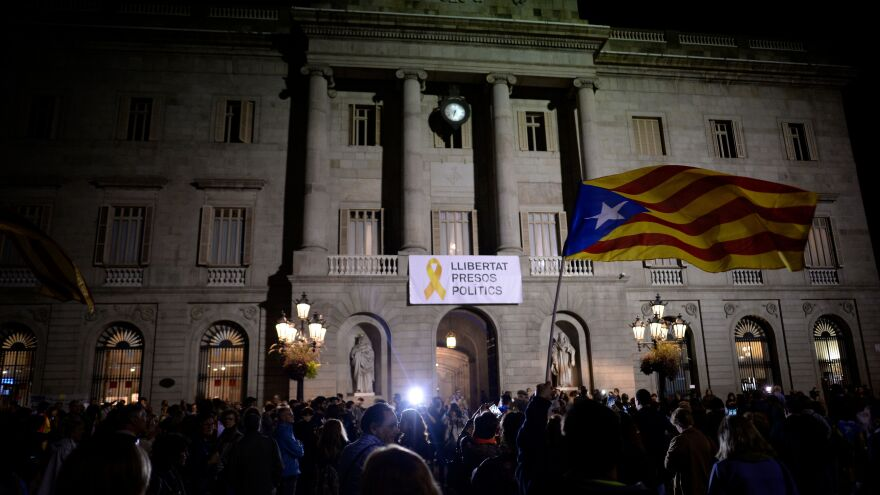 """A banner reading """"Freedom to political prisoners"""" hangs from City Hall in Barcelona as a protester waves a Catalan pro-independence Estelada flag during a demonstration on Friday to protest the detention of Catalan officials."""
