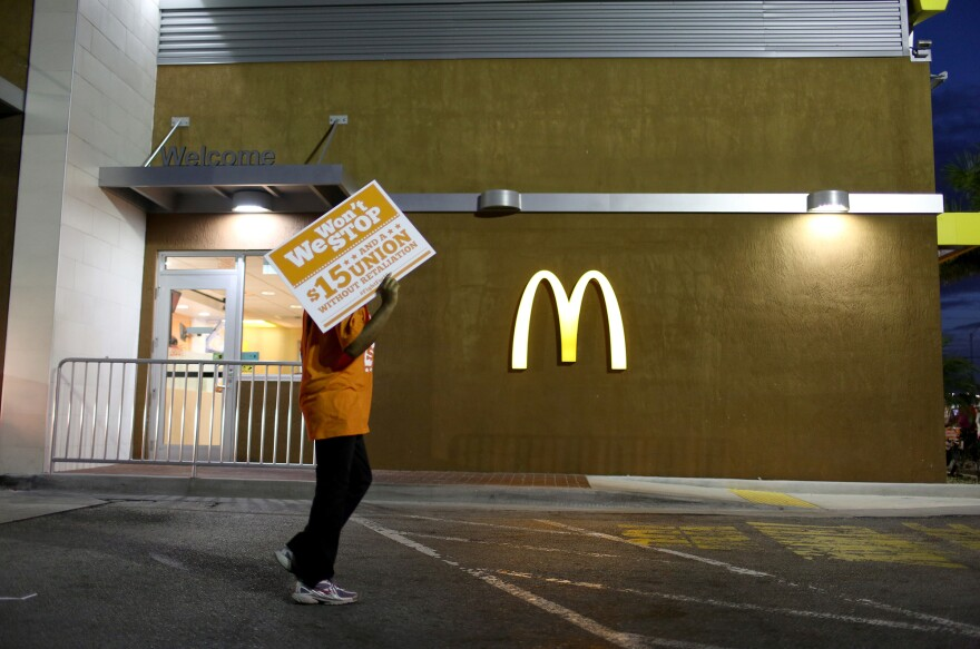"Protesters gather at a McDonald's to ask for higher wages on April 15, 2015 in Miami Gardens, Fla. Food labor advocate Saru Jayaraman writes in a new book that the company has taken the ""low road"" and lobbied extensively for lower wages and working conditions standards at the federal and state levels."
