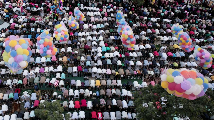 Egyptians gather on a city street in Cairo to pray beneath bunches of balloons.