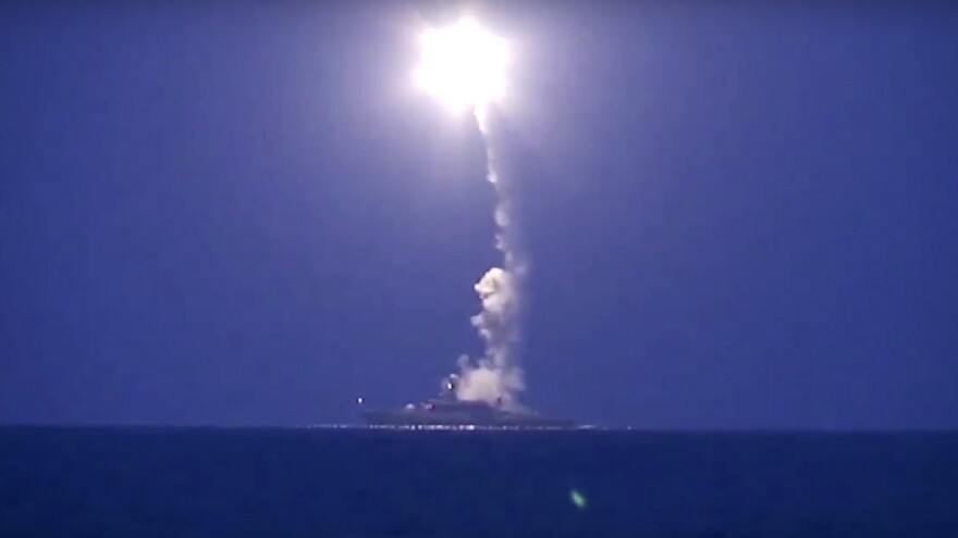A photo from Russian Defense Ministry footage shows a Russian navy ship launching a cruise missile in the Caspian Sea, sending it toward a target in Syria.