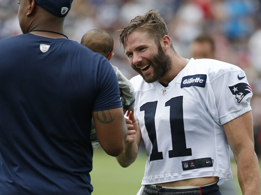 Patriots wide receiver Julian Edelman, who recently turned his personal story into a children's book, interacts with a baby following NFL football training camp in July 2017 in Massachusetts.