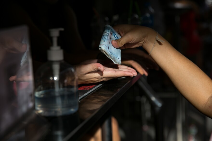At a bar in Pattaya, a woman receives a traditional Thai blessing for good luck. The symbolic gesture of having her hands patted with cash at the start of her shift is meant to help bring money into her hands that night.