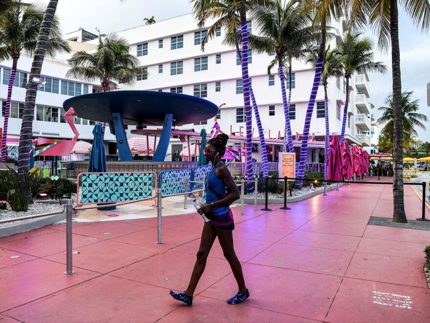 A woman walks past a closed restaurant this week in Miami Beach, Fla., during the coronavirus pandemic.
