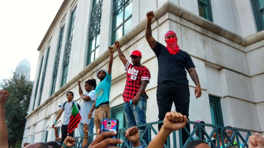 The police shooting of Keith Scott sparked protests that led to the creation of Charlotte Uprising. These protesters stood on a wall outside CMPD headquarters on Sept. 21, 2016.