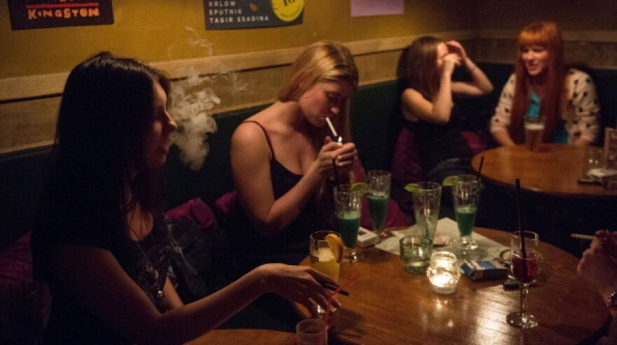 Women smoke in a Moscow bar in May. Tough new anti-smoking rules took effect Sunday in Russia, banning smoking in bars, restaurants and other public spaces.