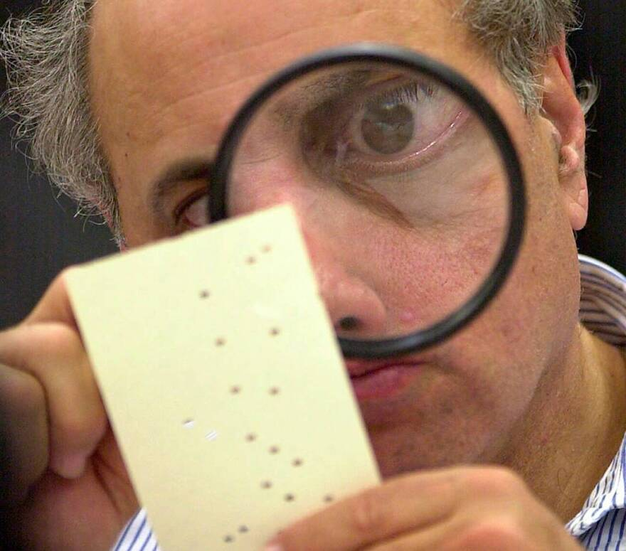 In this Nov. 24, 2000, file photo, Broward County, Fla. canvassing board member Judge Robert Rosenberg uses a magnifying glass to examine a disputed ballot at the Broward County Courthouse in Fort Lauderdale, Fla.