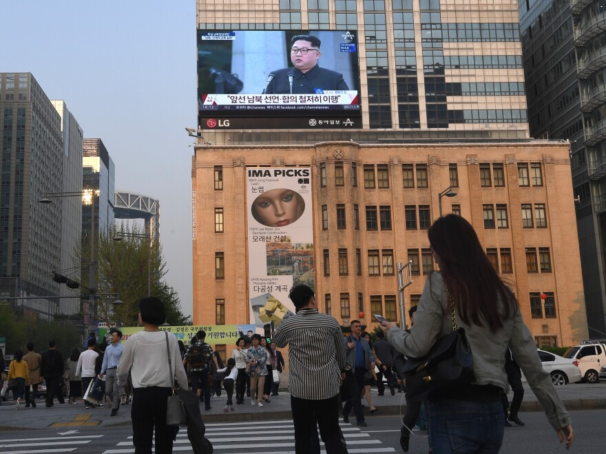 Pedestrians in downtown Seoul, South Korea, walk across the road as a big screen shows live footage of a joint news conference with Kim and Moon during the Inter-Korean Summit.