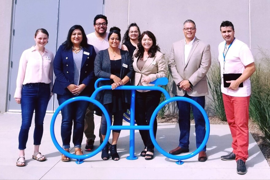 Eight commissioners pose for a picture in front of a blue bike sculpture.