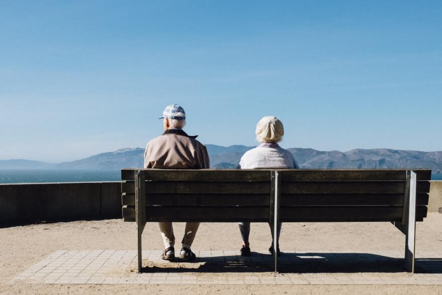 Man and woman sit on a bench facing the sea