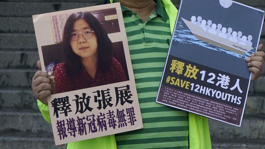 A pro-democracy activist holds placards with the picture of Chinese citizen journalist Zhang Zhan outside the Chinese central government's liaison office, in Hong Kong, Monday. Activists demand the release of Zhang, as well as the 12 Hong Kong activists detained at sea by Chinese authorities.