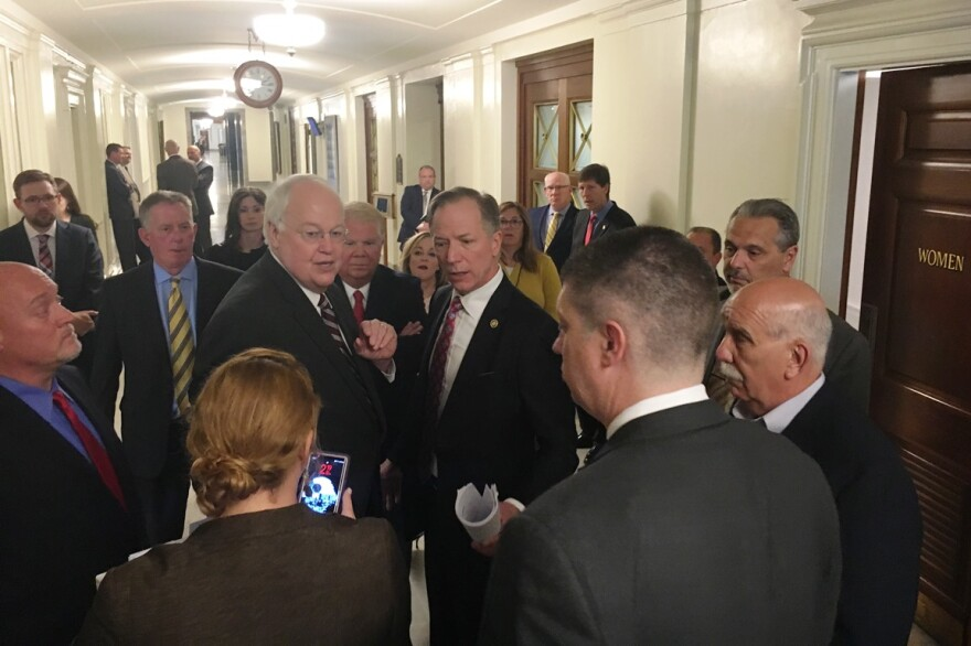 St. Charles County executive Steve Ehlmann, (facing the camera at left) speaks to two members of the Conservative Caucus, Sen. Bob Onder (facing camera at right) and Bill Eigel (back to camera) about incentives for GM.