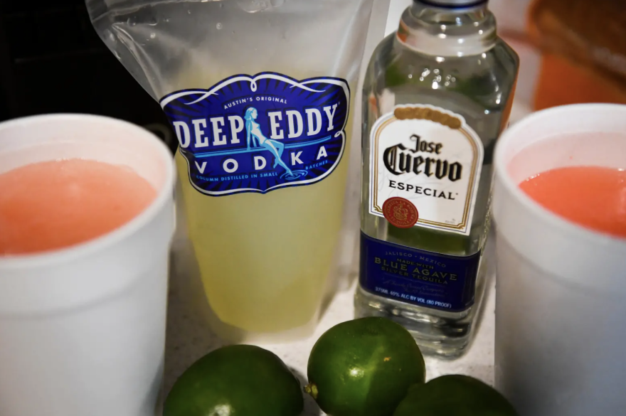 Liquor and Styrofoam cups of alcohol next to some limes.