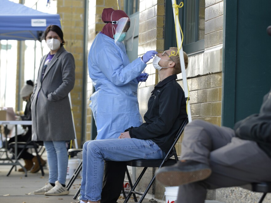 A medical staff member performs a COVID-19 test outside the Family Healthcare building in downtown Fargo, North Dakota, on Oct. 15. North Dakota is experiencing an influx in COVID-19 cases and on Nov. 6, the state reported a record high of 1,765 daily new cases.