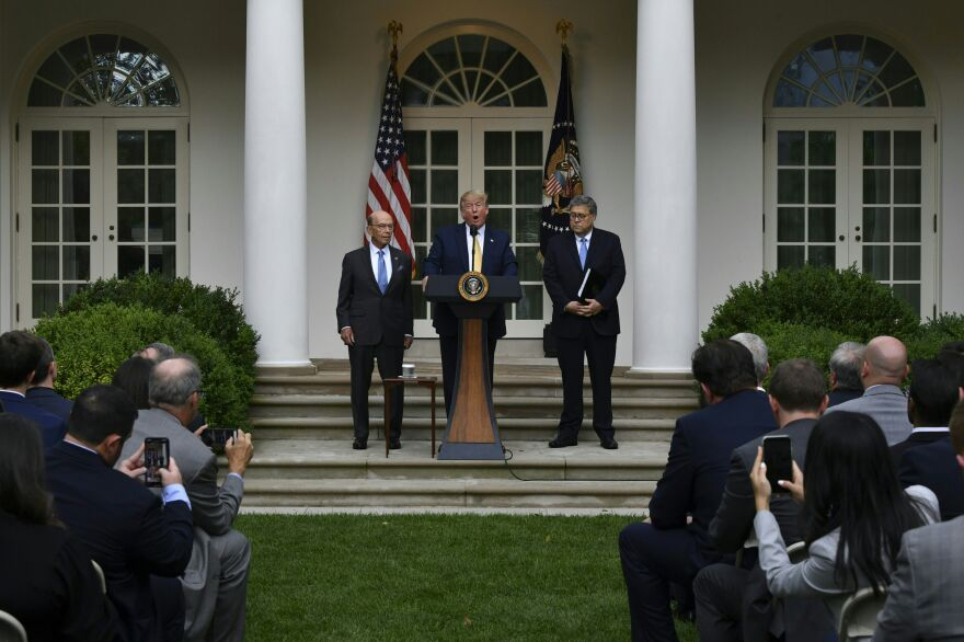 """At the 2019 White House Rose Garden announcement of an executive order for citizenship data, then-President Donald Trump was joined by then-Commerce Secretary Wilbur Ross (left) and then-U.S. Attorney General William Barr (right), who said the data """"may be relevant"""" to a lawsuit """"over whether illegal aliens can be included for apportionment purposes."""""""