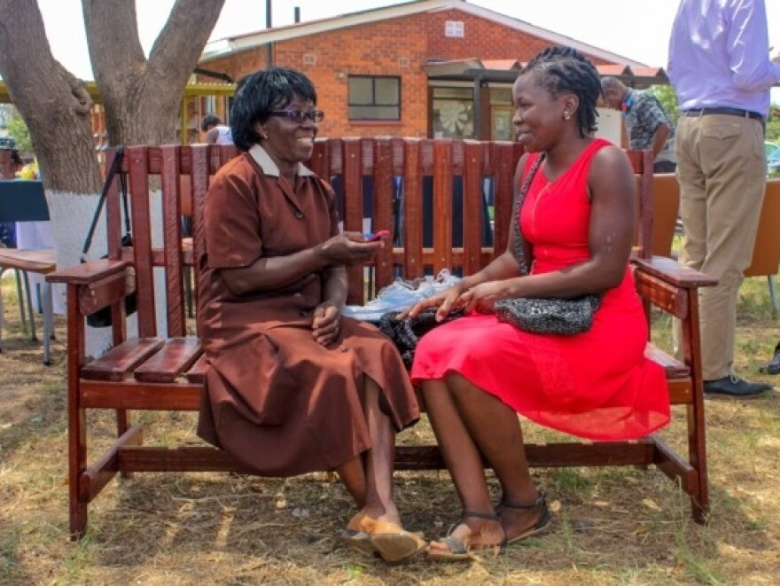 A community counselor, left, speaks to a patient on the Friendship Bench in Zimbabwe.