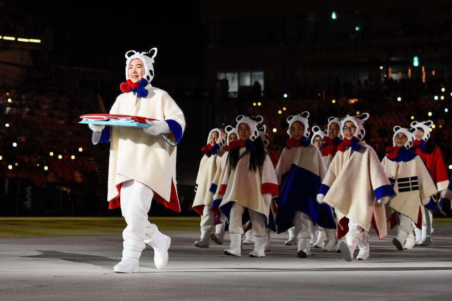 "Performers deliver a South Korean flag. Organizers had promised that the Olympic Stadium would be ""filled with the roar of compliments and the applause of friendship."""