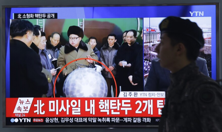 """A South Korean army soldier walks by a TV screen in March showing North Korean leader Kim Jong Un with superimposed letters that read: """"North Korea's nuclear warhead."""""""