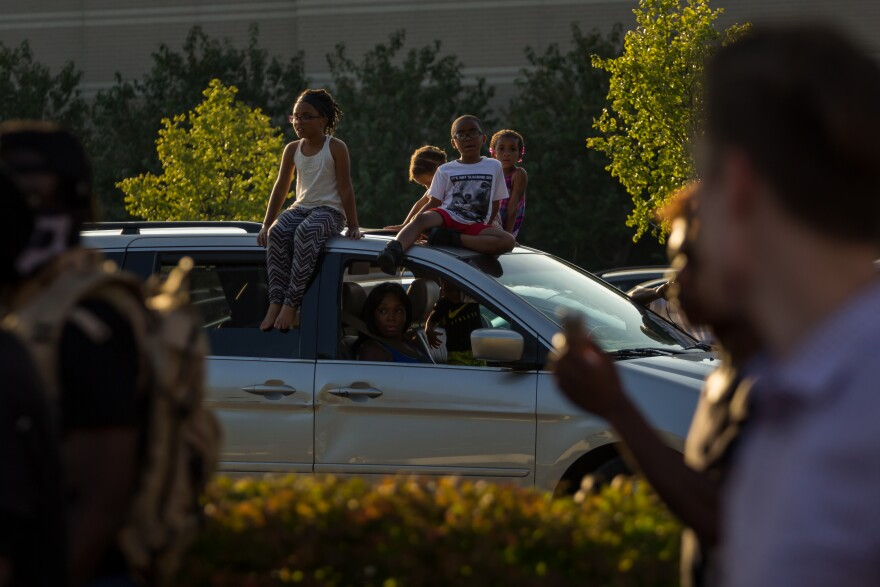 A family watches protesters march down Brentwood Blvd. in Richmond Heights on Sept. 20, 2017 from the parking lot of Galleria mall, which closed early for the evening.